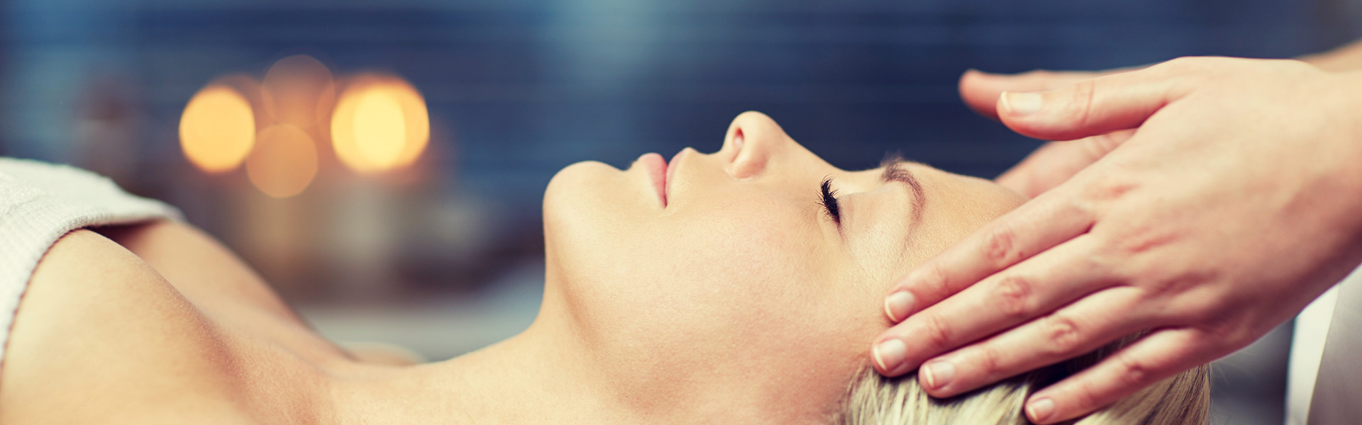 people, beauty, spa, healthy lifestyle and relaxation concept - close up of beautiful young woman lying with closed eyes and having face or head massage in spa
